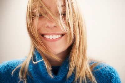 Beautiful Smiling Blond Woman with hair in face after 6 month smile by Spokane Dentist